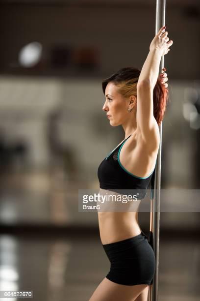 Profile view of a pole dancer in a studio.