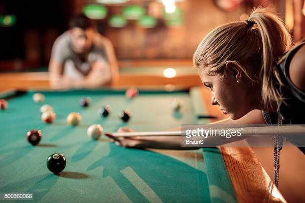 Profile view of a young woman aiming at pool ball.