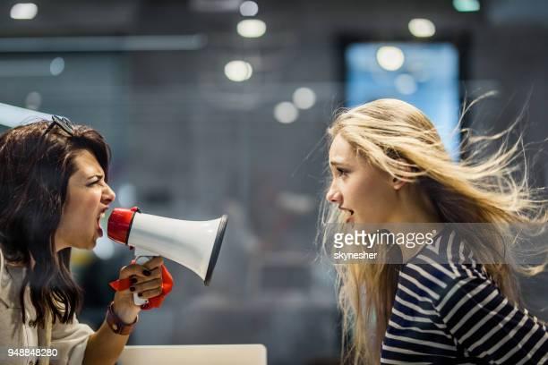 彼女の同僚にメガホンで叫んで怒っている女性マネージャーのプロファイルの表示。