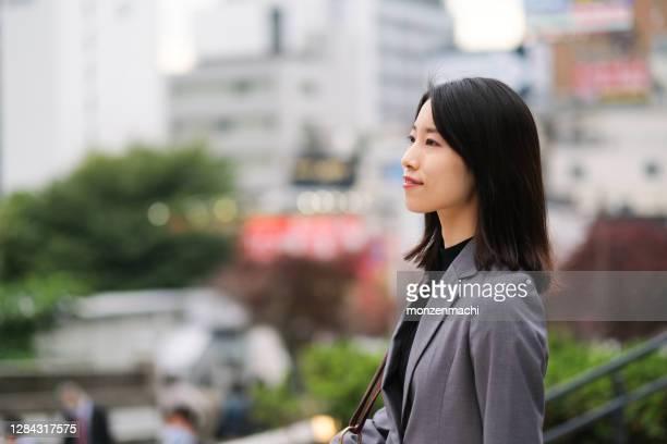 ダウンタウンの路上でのアジアの若い女性のプロフィール図 - businesswear ストックフォトと画像