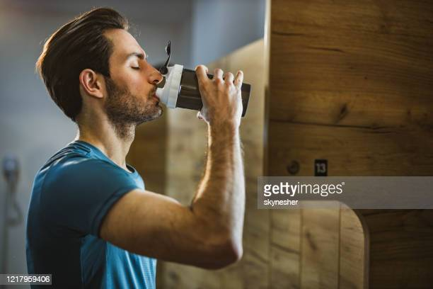 profile view of athletic man  drinking water in a gym's locker room. - backstage stock pictures, royalty-free photos & images