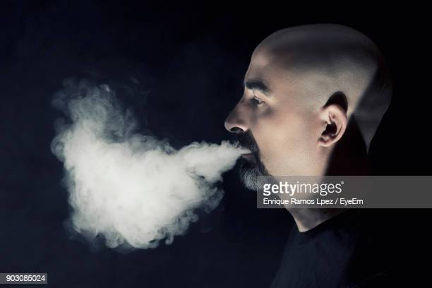 Profile View Of Bald Man Smoking Against Black Background