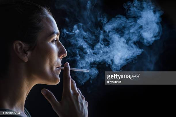 profile view of beautiful woman smoking in the dark. - cigarette stock pictures, royalty-free photos & images