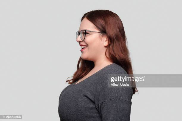 profile view of cheerful young woman with eyeglasses looking away with smiling facial expression over gray background - side view stock pictures, royalty-free photos & images