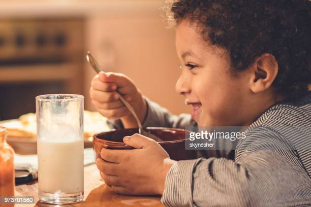 profile view of happy black boy eating breakfast at home. - breakfast cereal stock pictures, royalty-free photos & images