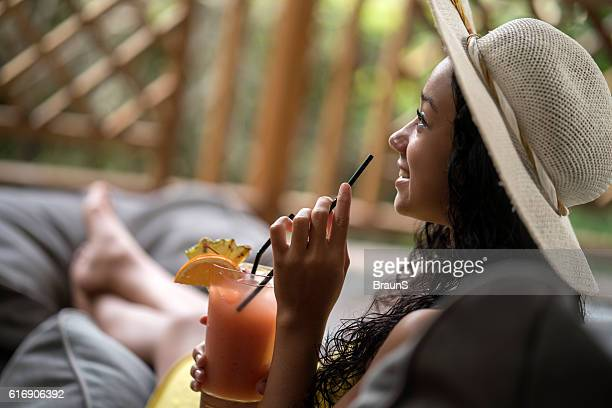 Profile view of happy Malaysian woman with fruit cocktail.