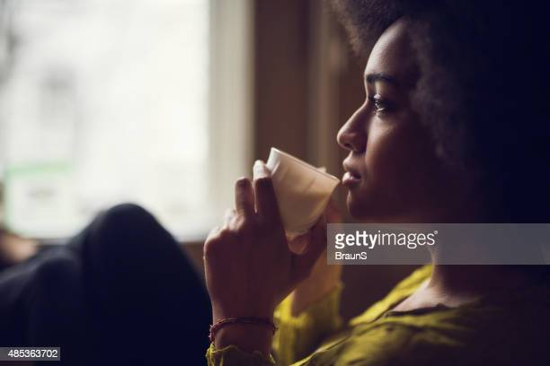 Profile view of lonely African American woman drinking coffee.