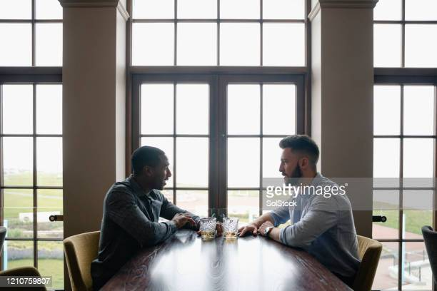 profile view of male friends at table with drinks - language stock pictures, royalty-free photos & images