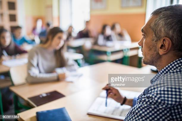 Profile view of mid adult high school teacher during the class.