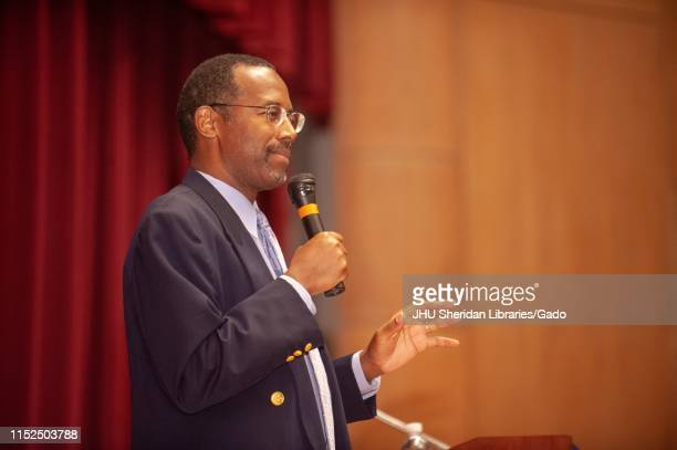 Profile view of neurosurgeon Ben Carson holding a microphone while speaking during a Milton S Eisenhower Symposium at the Johns Hopkins University...