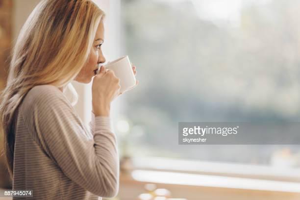 家庭で物思いにふける女性飲む朝のコーヒーのビューをプロファイルします。 - シンプルな暮らし ストックフォトと画像