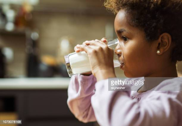 profile view of small black girl drinking milk at home. - milk stock pictures, royalty-free photos & images
