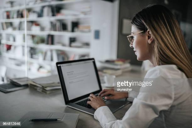 オフィスのノート パソコンに電子メールを入力する笑顔の実業家のビューをプロファイルします。 - %e... ストックフォトと画像