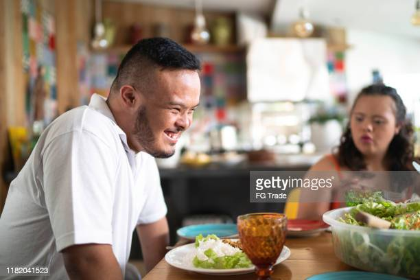 profile view of special needs boy laughing at lunch time - disabilitycollection stock pictures, royalty-free photos & images