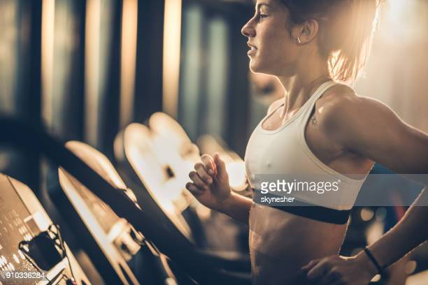 Profile view of sportswoman jogging on treadmill in a gym.