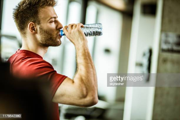 profile view of thirsty athletic man drinking water on a break in a gym. - só um homem imagens e fotografias de stock