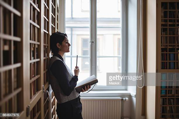 Profile view of thoughtful lawyer holding book while leaning on shelf in library