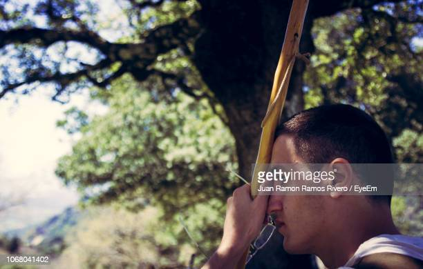 Profile View Of Thoughtful Man Holding Stick Against Trees