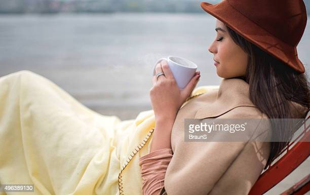 Profile view of woman enjoying in smell of hot chocolate.