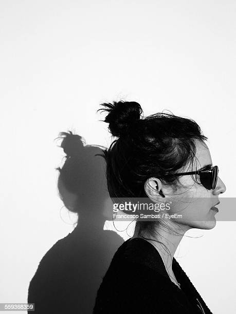 Profile View Of Woman Wearing Sunglasses Against Wall