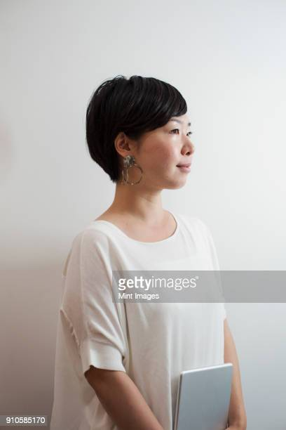 profile view of woman with sort black hair wearing white shirt standing in art gallery. - waist up stock pictures, royalty-free photos & images