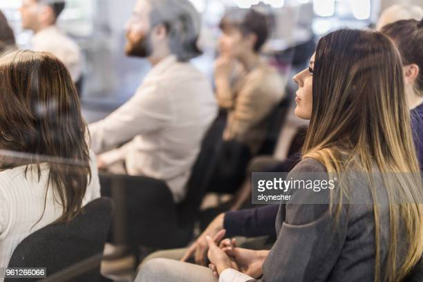 Profile view of young female entrepreneur on a business seminar in a board room.