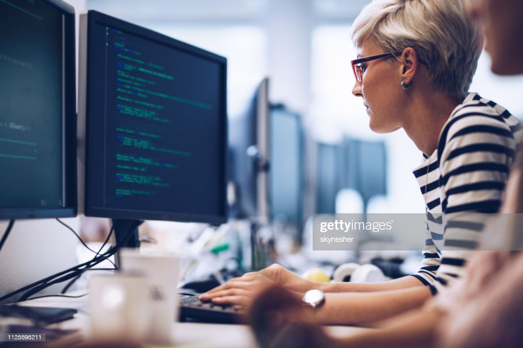 Profile view of young female programmer working on computer software in the office. : Stock Photo