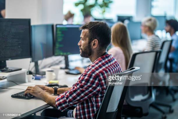 profile view of young programmer working on desktop pc in the office. - computer language stock pictures, royalty-free photos & images