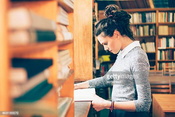 Profile view of young woman reading a book at library