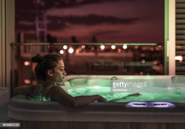 Profile view of young woman relaxing in a hot tub.