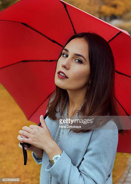 A profile view on woman in grey coat with red umbrella