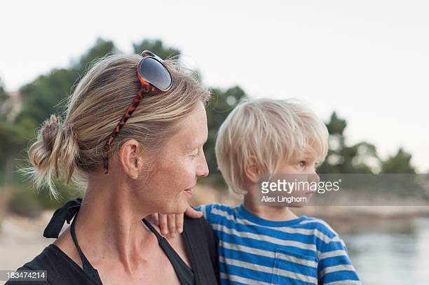 Profiles of blonde mother and toddler at a beach