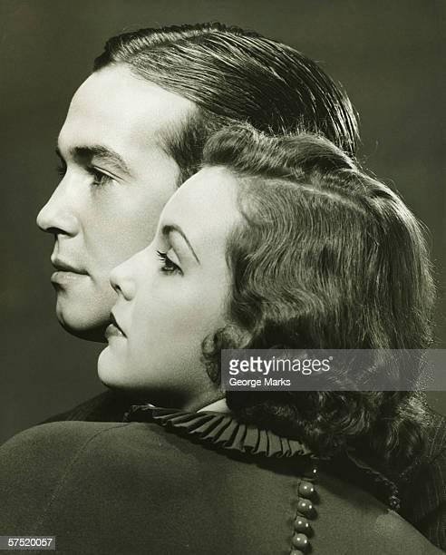 Profiles of couple posing in studio, (B&W), close-up, portrait