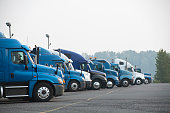 Profiles of different big rigs semi trucks standing in row on parking lot