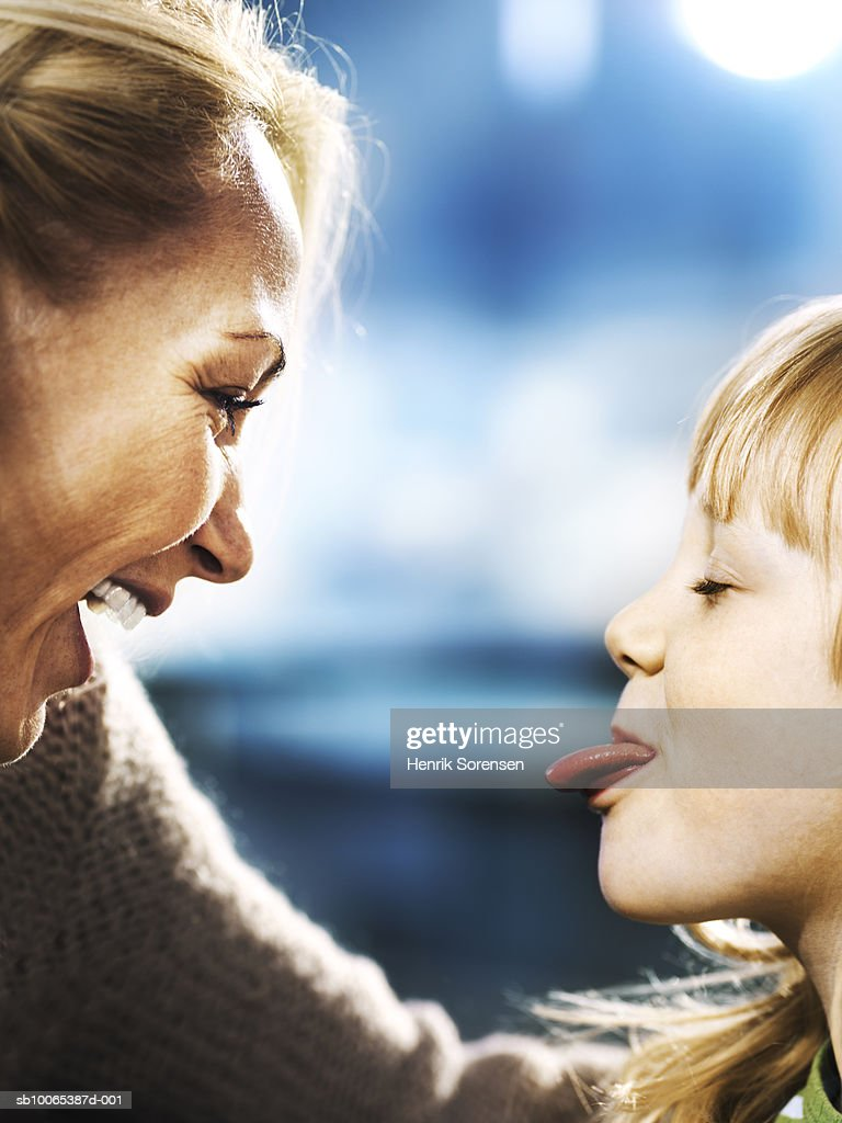Profiles of mother and daughter (6-7), girl sticking out tongue : Foto stock
