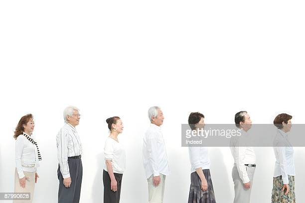 Profiles of senior men and women standing in a raw