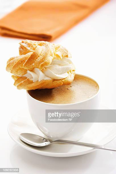Profiterole on cup of coffee, close-up