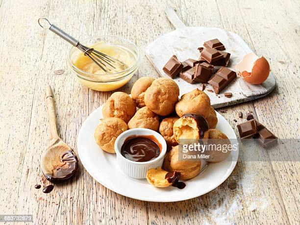 Profiteroles with hot chocolate sauce, chocolate pieces, egg