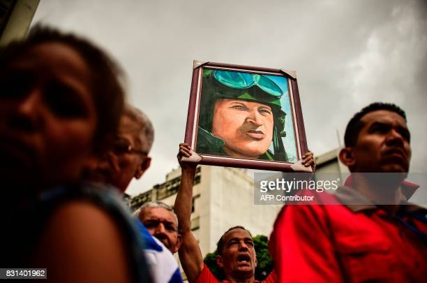 TOPSHOT A progovernment activist holds a portrait depicting late Venezuelan President Hugo Chavez during a demo to show their support to the...