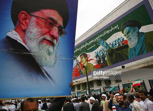 A progovernment demonstrator holds aloft a picture of Ayatollah Ali Khamenei at Tehran University on June 19 2009 in Tehran Iran Making his first...