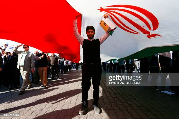 A progovernment demonstrator stands under an Iranian flag during a march in Iran's southwestern city of Ahvaz on January 3 as tens of thousands...