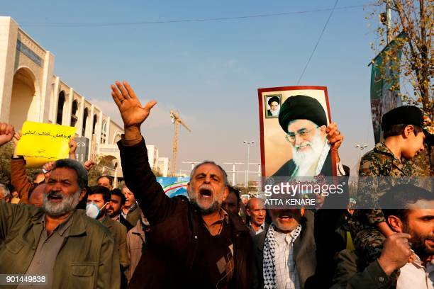 TOPSHOT Progovernment demonstrators hold a poster of Iran's supreme leader Ayatollah Ali Khamenei and Iran's founder of Islamic Republic Ayatollah...