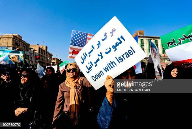 TOPSHOT Progovernment demonstrators hold banners during a march in Iran's southwestern city of Ahvaz on January 3 as tens of thousands gathered...