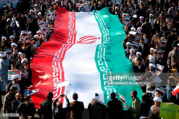Progovernment demonstrators wave their national flag during a march in Iran's holy city of Qom some 130 kilometres south of Tehran on January 3 as...