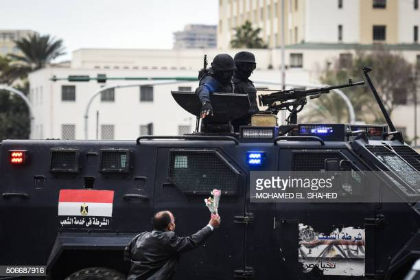 TOPSHOT A progovernment Egyptian man offers flowers to police special forces patrolling on Cairo's landmark Tahrir Square on January 25 as the...