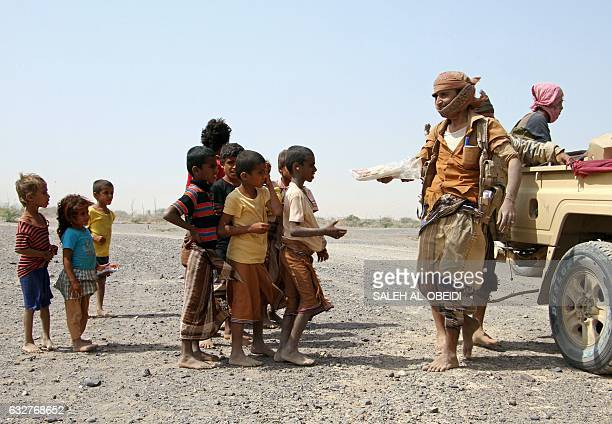 Progovernment fighters give food to Yemeni children on the road leading to the southwestern port city of Mokha on January 26 2017 Yemeni rebels are...