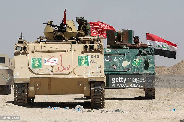 Pro-government forces drive in armoured personnel carriers as they engage in combat with the support of the Popular Mobilisation units in the...