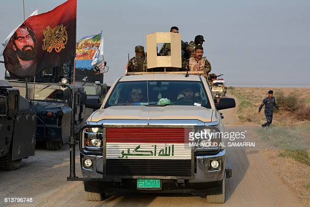 Progovernment forces drive in military vehicle in Iraq's eastern Salaheddin province south of Hawijah on October 10 as they clear the area in...