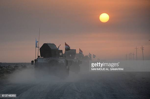 Progovernment forces drive in military vehicles in Iraq's eastern Salaheddin province south of Hawijah on October 10 as they clear the area in...