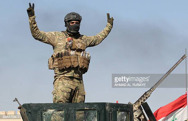 A progovernment forces fighter flashes the sign for victory near alSejar village in Iraq's Anbar province on May 26 as they take part in a major...